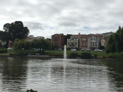 A view of a fountain and unique San Francisco buildings in the background.