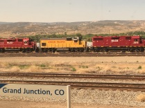 Freight trains stand in front of mountains in Grand Junction, Colorado.