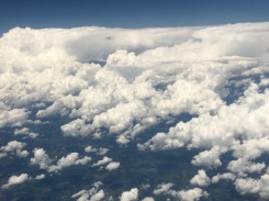 A giant wall of clouds outside of the plane window.