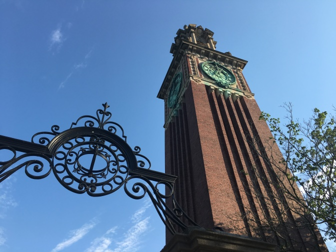 The gate entrance stands below the memorial clock tower built on campus grounds.